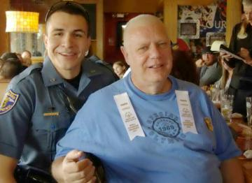 """Jason"", a Colorado State Trooper, shares the camera with a Special Olympian"